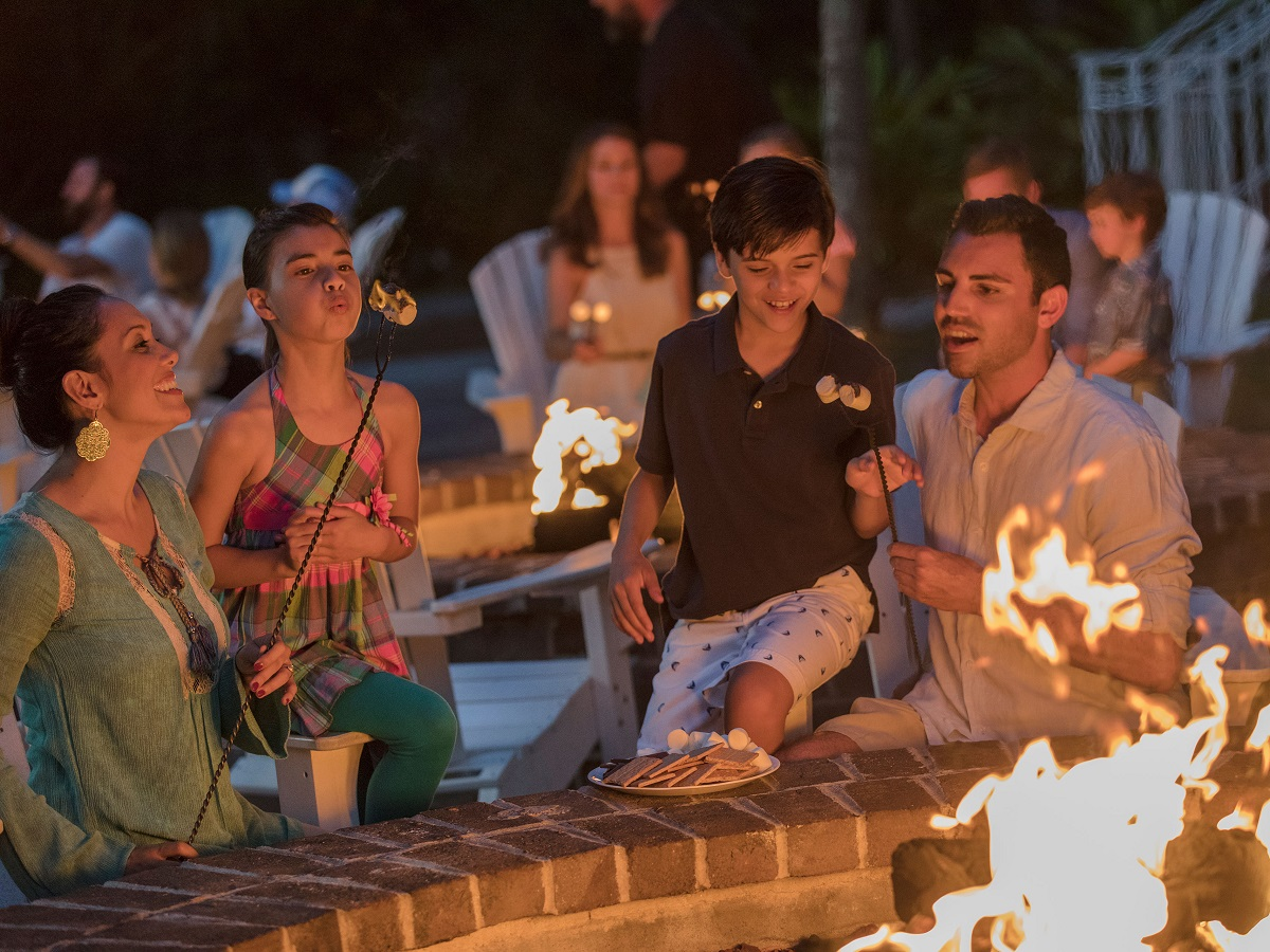 Family having fun roasting marshmellows at a Marriott Vacation Club timeshare resort.